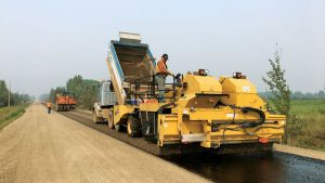 Applying sealcoat to gravel road
