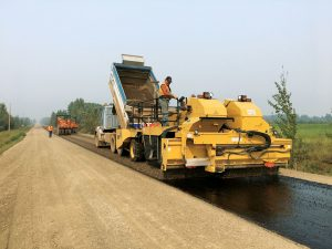 Applying sealcoat to a gravel road