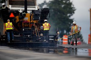 paving crew applying asphalt to a new road bed