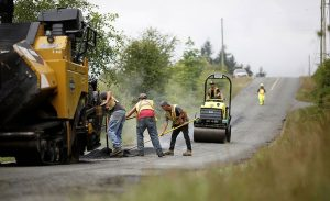 paving crew patching a narrow rural road