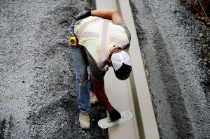 Worker smoothing a formed concrete curb