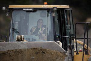 female paving crew member operating front end loader