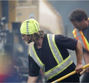 Crew member spreading asphalt